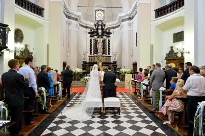 Coppia di sposi fotografata all'interno di una chiesa luminosa